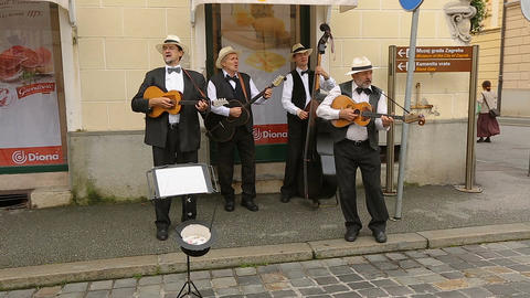 Street musicians playing guitars and singing songs, performance, music in Zagreb Footage