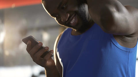 Shy handsome man reading message on smartphone with smile on face, flirting Live Action