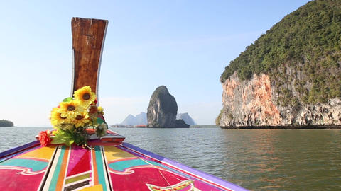 Ornamented Longtail Boat Sails up to Village near Cliff Footage