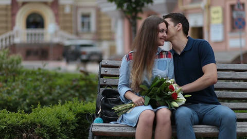 Attractive dating couple sitting on bench in park Footage