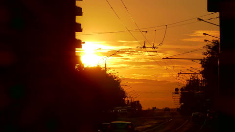 4K Passenger Trolleybus Crosses Frame Against Sunset in Evening City With Footage
