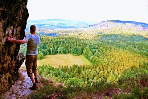 Tall tourist climbing on sharp cliff and overlooking beautiful view above forest フォト