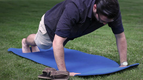 Man doing wimpy wrong form pushups on yoga mat in park Footage