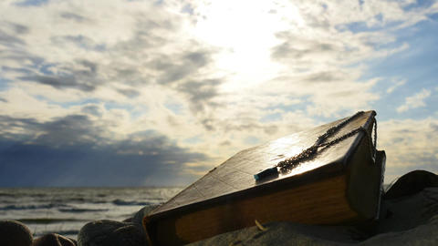 Old Bible left at sea shore clouds motion time lapse Archivo