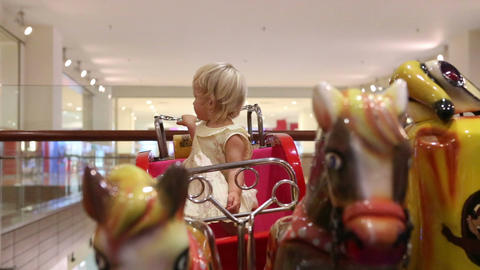 Little Blonde Sitting in Toy Coach with Horses Footage