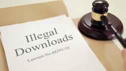 Illegal downloads lawsuit documents with gavel placed on desk of judge in court Footage