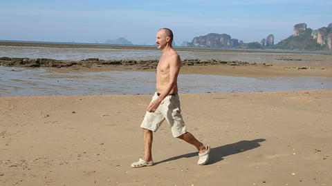 Old Man Jogs along Beach at Low Tide Footage