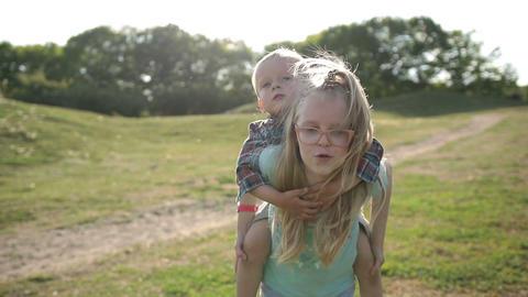 Cute girl giving toddler boy piggyback ride in park Footage