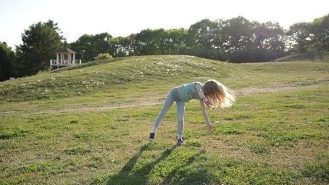 Cute teenage girl doing cartwheel at green meadow Footage