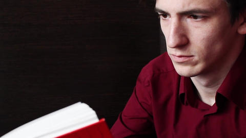 A young guy in a red shirt calmly reads a red book
