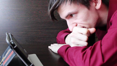 A young guy looks at the tablet on the table flips through the page Footage