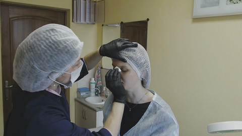 The employee of the cosmetology clinic makes manipulations on the coloring of th Footage