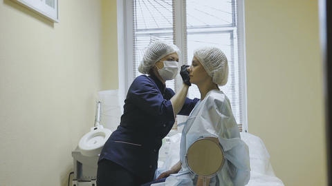 A female employee of a cosmetology clinic makes markup before the microblasting Footage