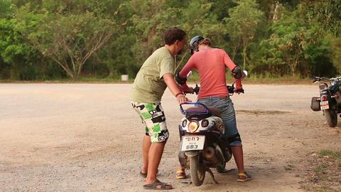 Instructor Helps Girl in Helmet Lower Scooter Footage