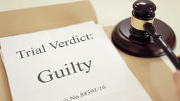 Trial verdict folder with gavel placed on desk of judge in court Footage