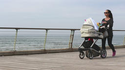 Woman walking along the beach with baby Footage