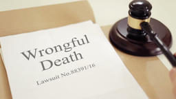 Wrongful death lawsuit documents with gavel placed on desk of judge in court Footage