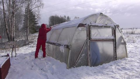 Gardener cleaning removing snow from plastic greenhouse Footage