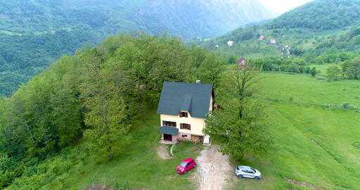 Beautiful house in the mountains surrounded by trees. Aerial.s Footage