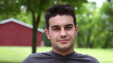 Handheld portrait shot of young handsome italian male smiling at camera Footage
