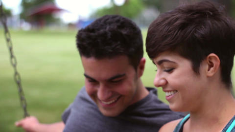 Attractive Millennial couple on swing in park looking at smartphone and laughing Footage