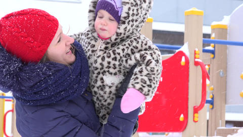 Happy mother and baby child have fun under snow blizzard in playground Footage