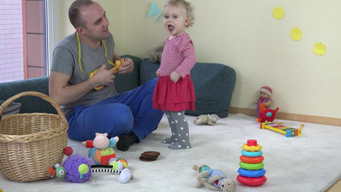 Father man play with toy guitar and happy toddler daughter girl dance at home Footage