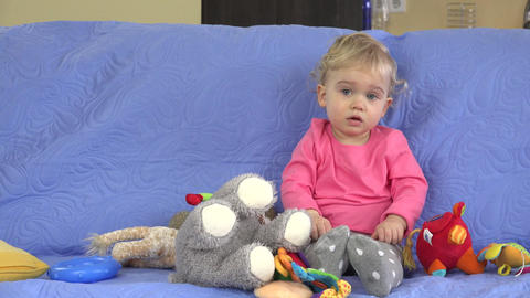 Little baby girl throwing soft toys from sofa Footage