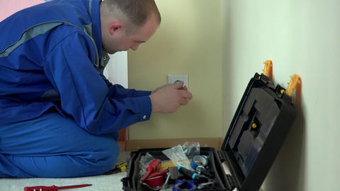 Worker electrician repair wall socket in apartment Live Action