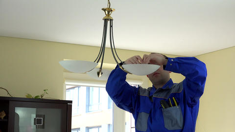 Experienced electrician changing light bulbs at client home Footage