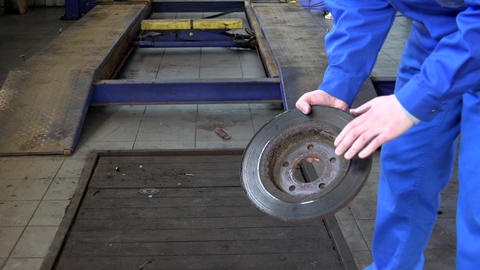 mechanic hands showing worn rusty brake disk at garage Footage