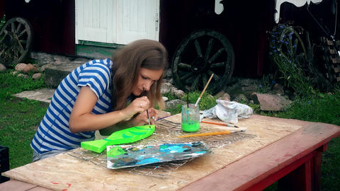 Young woman painting fish decoration on wooden table in house yard Footage