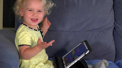 Emotional little girl playing game with tablet computer Footage