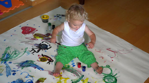 Funny little girl painting on floor at home Footage