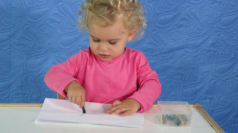 Child painting with crayon pencil on paper at home Footage