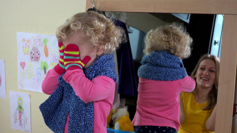 Playful little girl and her mother playing near mirror Footage