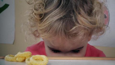 Beautiful girl eating with pleasure crispy corn circles Footage