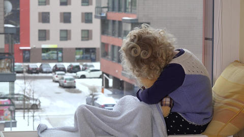 Kid with best friend teddy bear caress and kiss looking at snow fall blizzard Footage