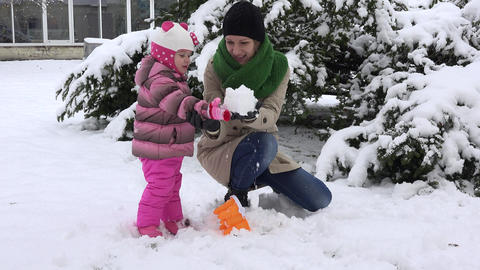 Playful mother with excited daughter girl build snow castle and destroy it Footage