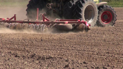 Tractor plowing field with dust rising on sunny day Footage