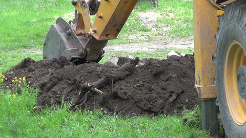 Industrial excavator digging a hole on lawn Footage