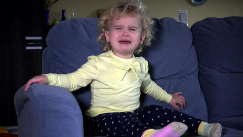Stressed cute little girl crying sitting on sofa Footage