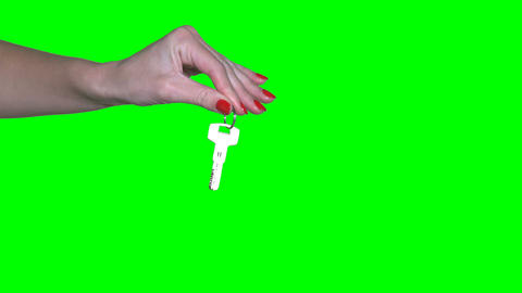 female realtor seller hand holding key isolated on green even background Footage