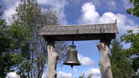 Metal bell hanging under wooden park gate roof Filmmaterial