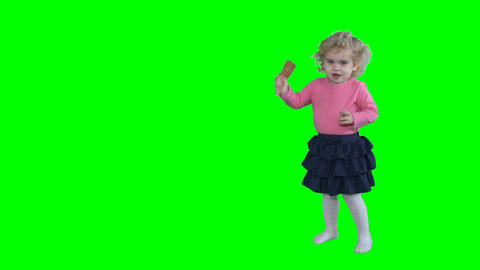 Cute little girl put golden party glasses on head isolated on green Live Action