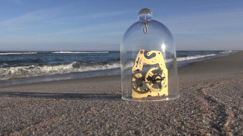 Clock mechanism by sea on beach sand with glass piece Footage