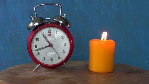 Retro alarm clock with burning candle Footage