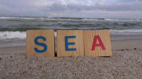 "Word ""sea"" written with letter cubes on beach ビデオ"