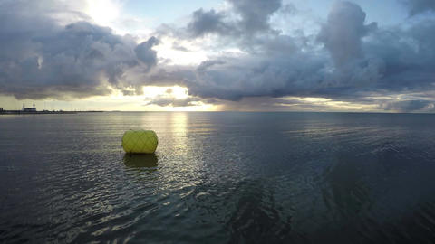 yellow buoy on early morning sea water near coastline and wind Footage