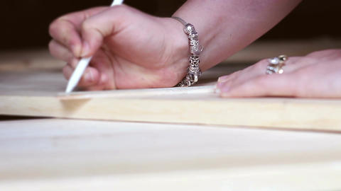 Woman traces along a wooden plank with a pen for a woodshop project - V1 Footage